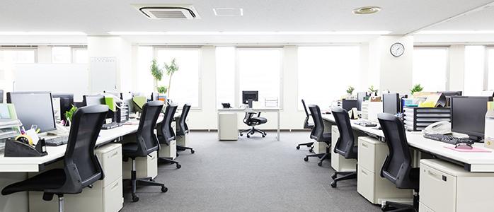 机とパソコンが並ぶオフィス風景