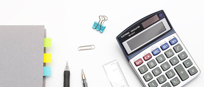 机の上に並んだ電卓とノートとボールペン