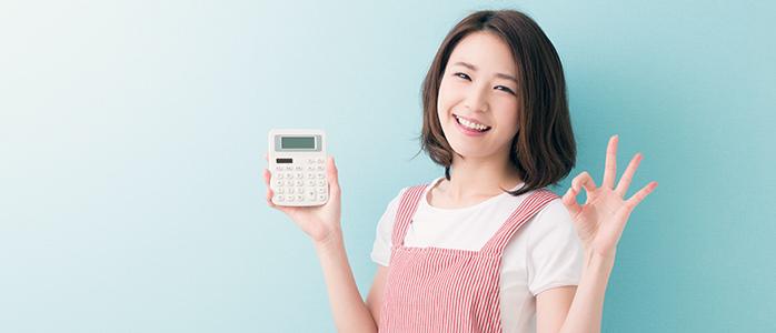 電卓を手に持ってOKサインを作るエプロン姿の女性