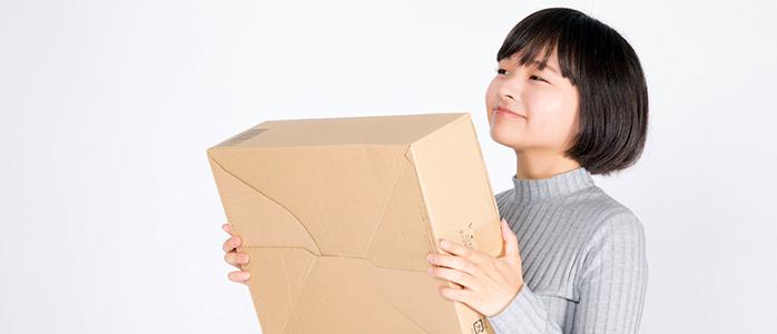 ネットショップで購入した商品を受け取り笑顔を見せる女性