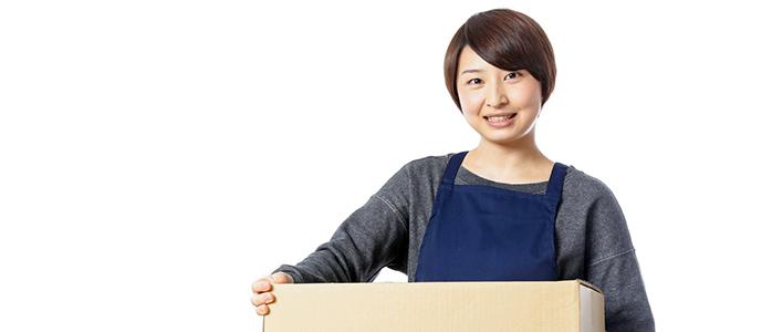 段ボール箱を持つハンドメイド作家の女性