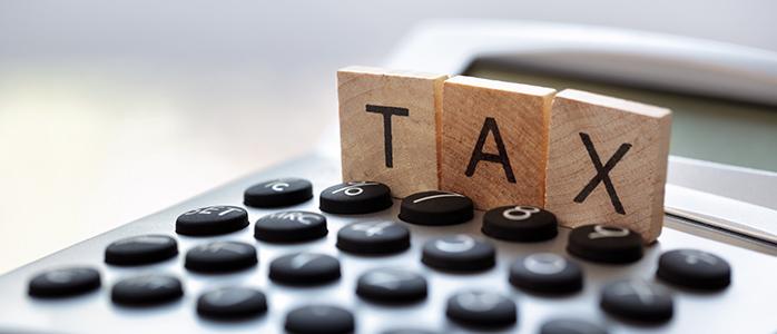 電卓の上に並ぶ「TAX」の文字