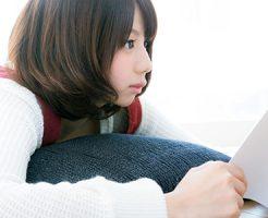寝そべってテレビを見ながら読書をする若い女性