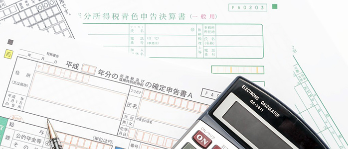 確定申告書Aと所得税青色申告決算書の上に置かれた電卓