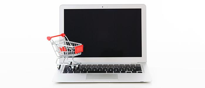 ノートパソコンの上に置かれたショッピングカートの模型
