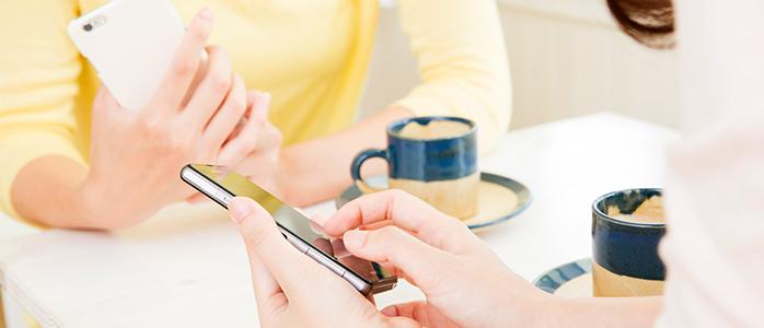 カフェでスマートフォンを操作する主婦友だち