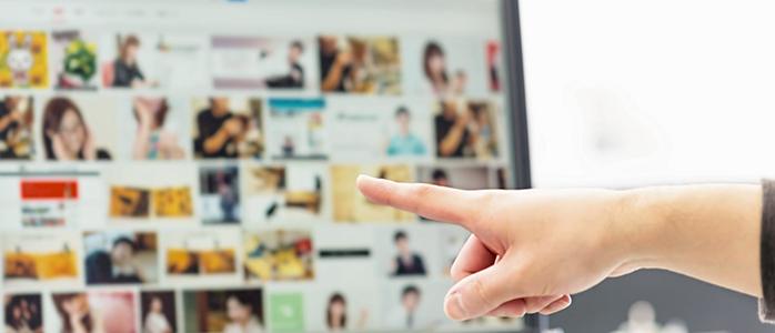 画像検索の検索結果が表示されたモニターを指差す女性