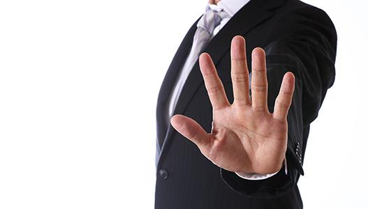手で制止の合図を出すスーツ姿の男性