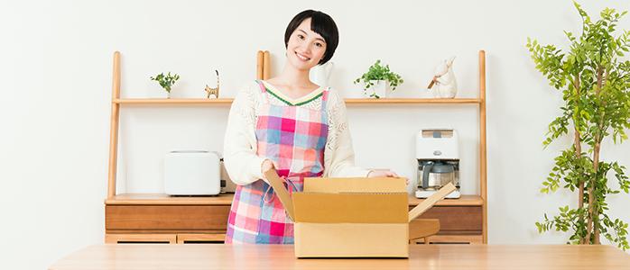 発送用段ボール箱の前で笑顔を見せる主婦