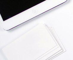 iPadと並べて置かれたショップカードの束