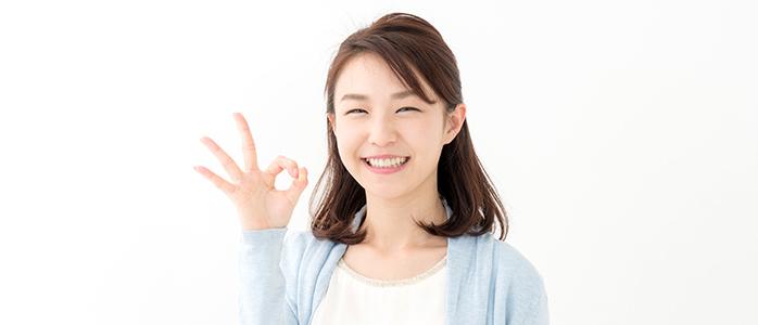 笑顔でオーケーサインを作る若い女性