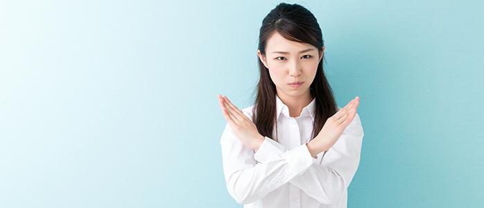 手でNGサインを作る若い女性
