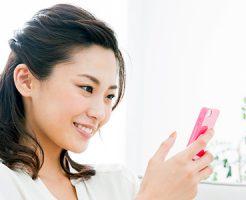 スマホを操作する笑顔の女性